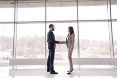 Business People Shaking Hands against Window royalty free stock image