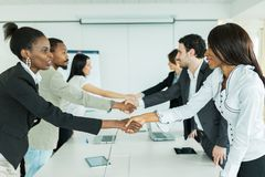 Business people shaking hands as a sign of greeting. Business people shaking hands before sitting down to a conference table stock photography