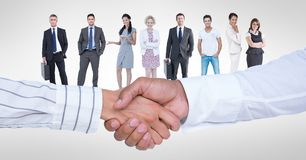 Business people shaking hands with colleagues in background. Digital composite of Business people shaking hands with colleagues in background Royalty Free Stock Image