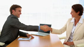 Business people shaking hands at desk. In the office stock video