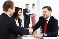 Business people shaking hands, finishing up meeting. Business people shaking hands, finishing up a meeting Royalty Free Stock Image