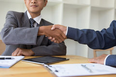 Business people shaking hands after finishing up a meeting. Gree Royalty Free Stock Image