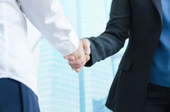 Business people shaking hands, finishing up a meeting with modern building background. royalty free stock photo