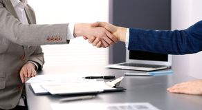 Business people shaking hands, finishing up a meeting. Papers signing, agreement and lawyer consulting concept.  Royalty Free Stock Images
