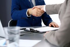Business people shaking hands, finishing up a meeting. Papers signing, agreement and lawyer consulting concept.  Stock Photo