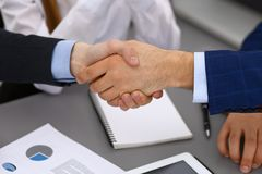 Business people shaking hands, finishing up a papers signing. Meeting, agreement and lawyer consulting concept.  Royalty Free Stock Images