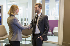 Business people shaking hands in lobby Royalty Free Stock Images