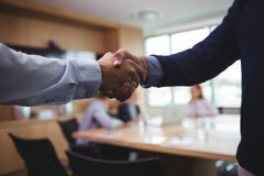 Business people shaking hands during meeting in board room. Cropped image of business people shaking hands during meeting in board room Royalty Free Stock Images