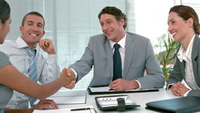 Business people shaking hands during meeting. In slow motion