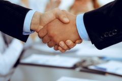 Business people shaking hands at meeting while theirs colleagues clapping and applauding. Group of unknown businessmen royalty free stock images