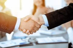 Business people shaking hands at meeting while theirs colleagues clapping and applauding. Group of unknown businessmen royalty free stock photo