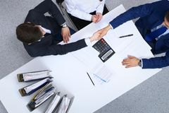 Business people shaking hands at meeting, view from above. Bookkeeper or financial inspector making report, calculatin. G or checking balance. Internal Revenue royalty free stock photography