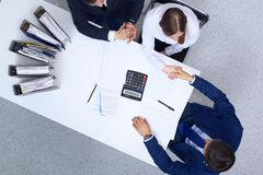 Business people shaking hands at meeting, view from above. Bookkeeper or financial inspector making report, calculatin. G or checking balance. Internal Revenue royalty free stock images