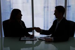 Business people shaking hands at office desk Stock Image