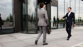 Business people shaking hands. Outdoor office building and walking inside together stock footage