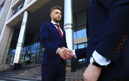 Business people shaking hands outside modern office building. Stock Photos