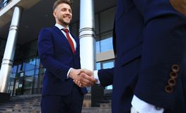 Business people shaking hands outside modern office building. Royalty Free Stock Photography