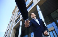 Business people shaking hands outside modern office building. Stock Image