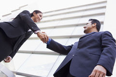 Business people shaking hands outside office Stock Photo