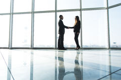 Business people shaking hands over office background Royalty Free Stock Photo