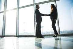 Business people shaking hands over office background Stock Images