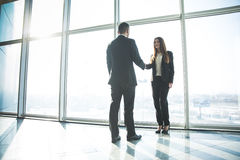 Business people shaking hands over office background Stock Photo