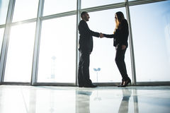 Business people shaking hands over office background Stock Photos
