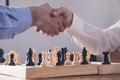 Business people shaking hands. Playing chess game stock photo