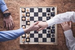 Business people shaking hands. Playing chess game royalty free stock images