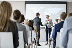 Business people shaking hands during seminar at convention center Royalty Free Stock Photos