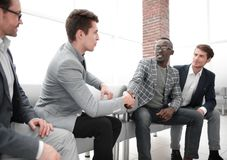 Business people shaking hands sitting in the lobby of the business center royalty free stock photos