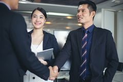 Business people shaking hands and smiling their agreement to sign contract and finishing up a meeting stock image