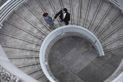 Business People Shaking Hands On Spiral Staircase Stock Photo