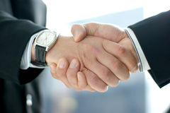 Business people shaking hands together. Business people are shaking hands together in order to show success. Image taken on an abstract background Stock Image