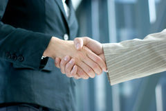 Business people shaking hands together. Business people are shaking hands together in order to show success. Image taken on an abstract background Royalty Free Stock Image
