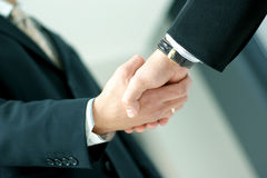 Business people shaking hands together. Business people are shaking hands together in order to show success. Image taken on an abstract background Stock Photography