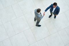 Business People Shaking Hands, Top View. Top view of two business people shaking hands standing on tiled floor in hall of modern office building, copy space Royalty Free Stock Photography