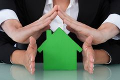 Business People Sheltering House Model In Office. Cropped image of business people sheltering green house model in office Stock Photos