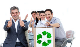 Business people showing the concept of recycling. Cheerful business people showing the concept of recycling against a white background Stock Photos