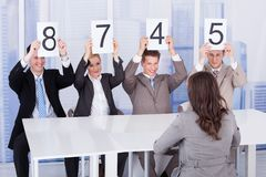 Business people showing score cards in front of female candidate Stock Images