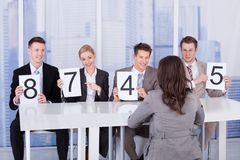 Business people showing score cards in front of female candidate Stock Image