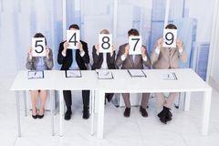 Business people showing score cards Stock Photos