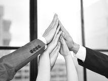 Business people showing team spirit and determination. Businesspeople putting hands together to form a pyramid in a display of team spirit and determination royalty free stock images