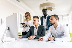 Business people showing team work while working in board room in office interior. People helping one of their colleague to finish stock image
