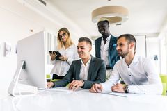 Business people showing team work while working in board room in office interior. People helping one of their colleague to finish royalty free stock photo