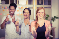 Business people showing thumbs up in office Stock Images