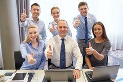 Business people showing thumbs up in office Stock Photo