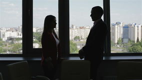 Business people silhouette, man standing near window and talks with woman. stock video