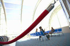 Business people sitting in airport departure lounge, focus on rope barrier in foreground (tilt) Stock Photography