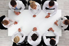 Business people sitting around empty table stock photos